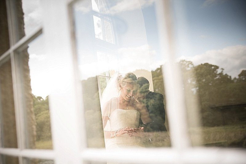 Bride and groom sit secluded by themselves in a summer house