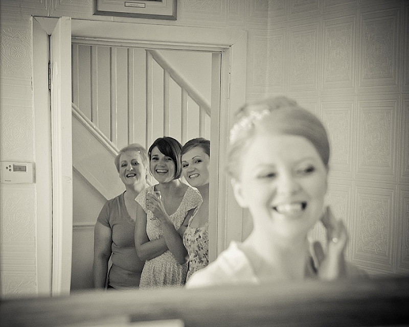 Bridesmaids look on at bride getting ready
