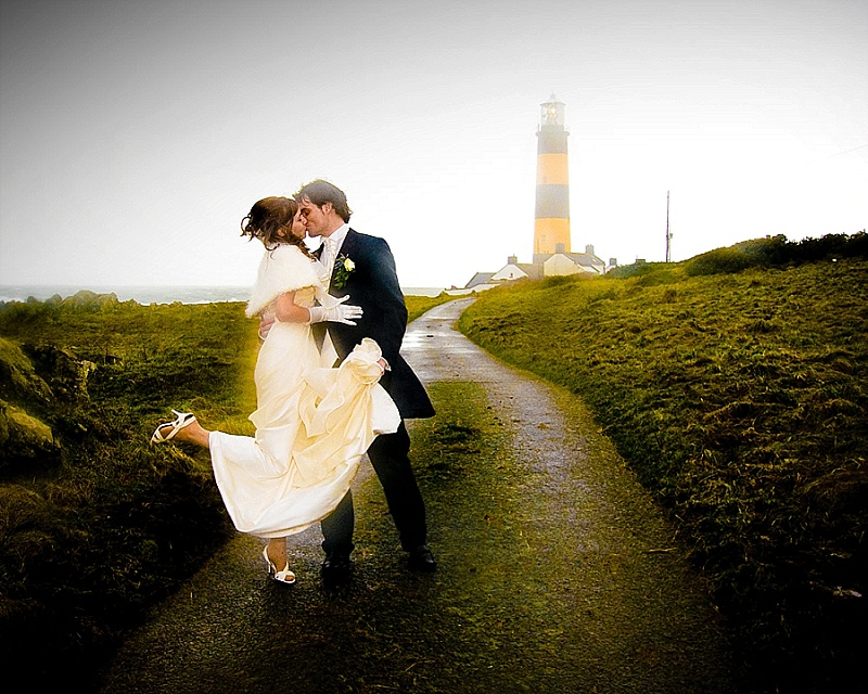 Wedding couple kiss in dramatic lighthouse picture