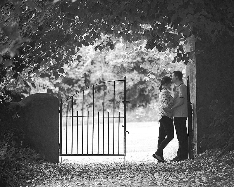 Black and white image of couple kissing against gate