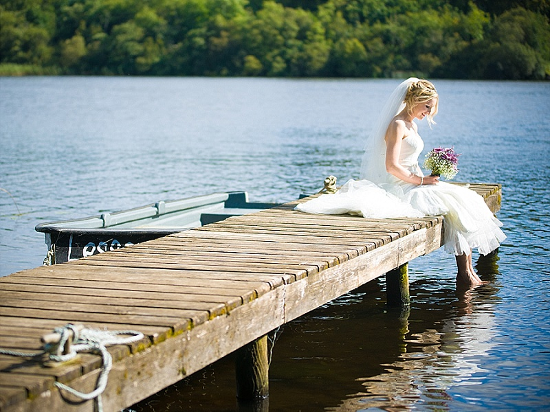 Bride sits on her own on a pier with feet in the water