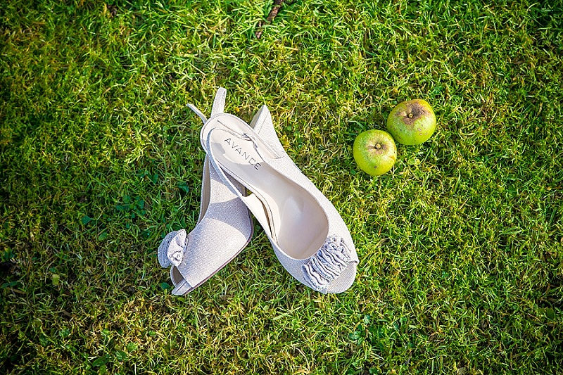 Wedding shoes lie on the ground with apples