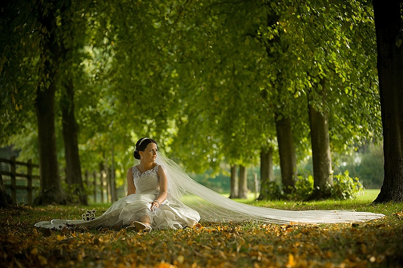 Bride sits on ground with long veil