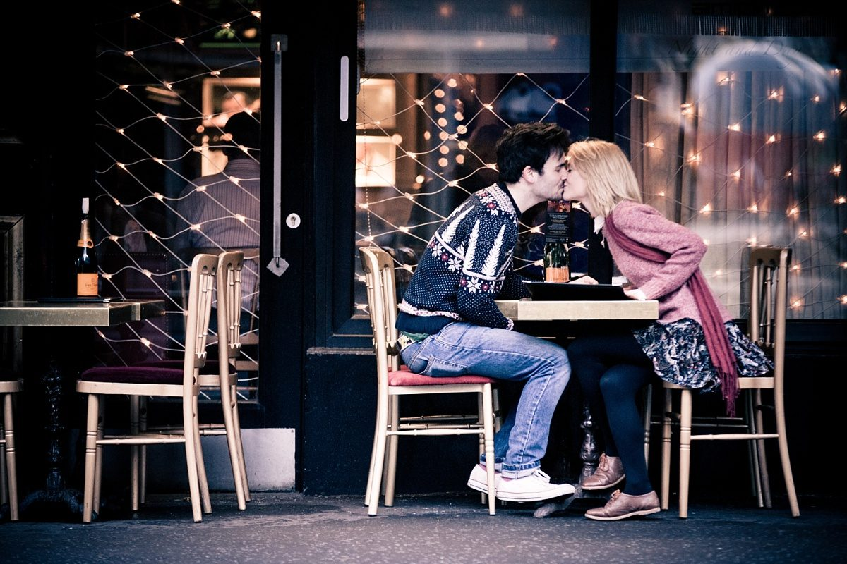 Engaged couple kiss over dinner
