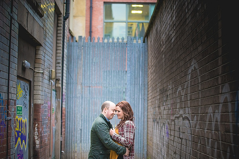 Engaged couple kiss in an alley way