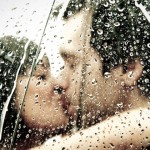 Young newly married couple embrace under an umbrella soaked in rain