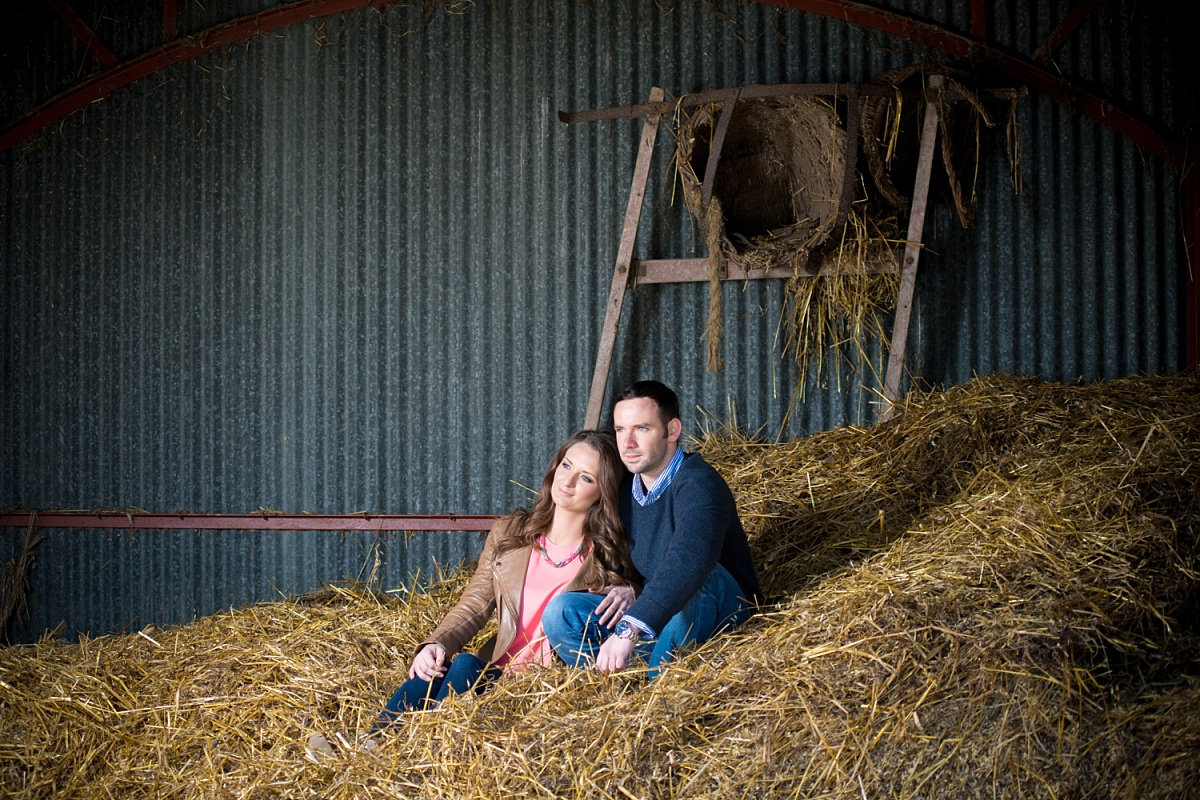 Engaged couple sit on massive pile of hay