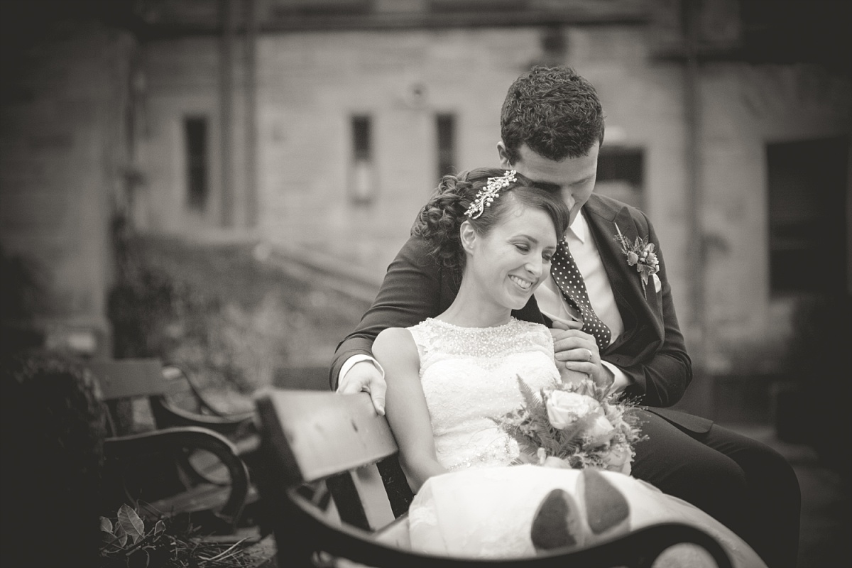 Couple sit hugging on their wedding day on bench in black and white
