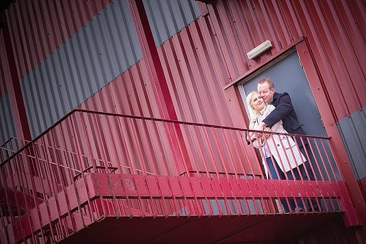 Engaged couple kiss on abandoned stairwell