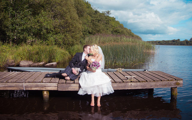 Newly married couple embrace on a river wooden pier