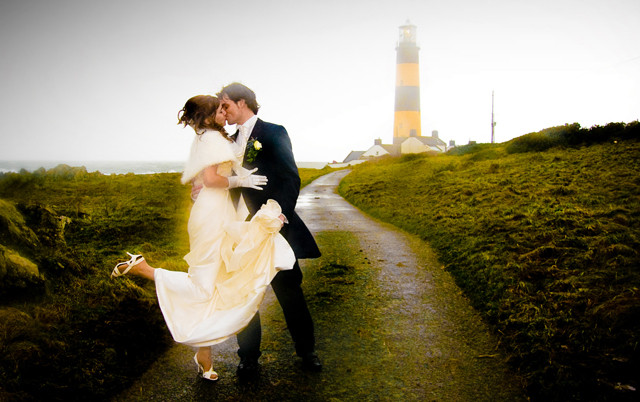 Wedding photo of newly married couple kissing with a lighthouse in the background