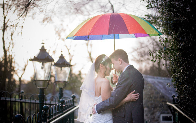 Married couple embracing under an umbrella