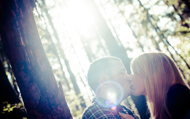 Photo of a young couple kissing under the morning sunshine