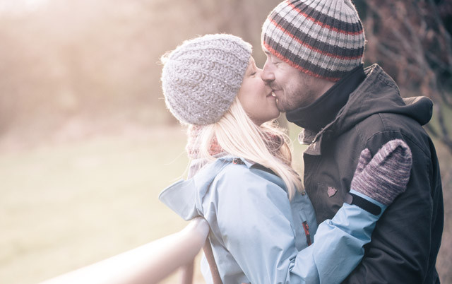Young engaged couple kissing on a cold day