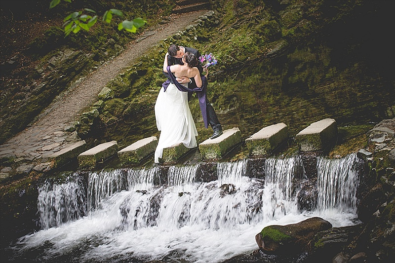 Bride and groom kiss on stepping stones over waterfall