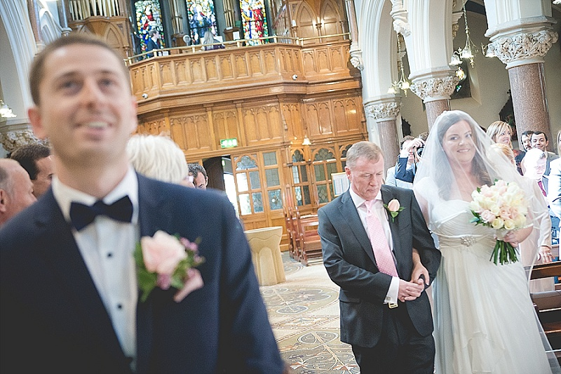 Bride entering church with father and groom waiting