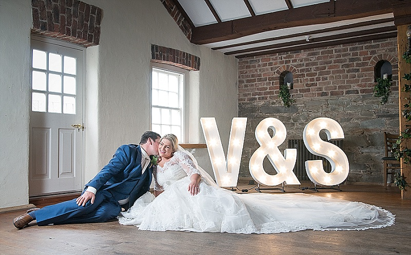 Bride sits on floor in front of large illuminated letters