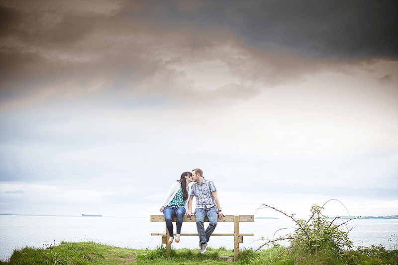 Coastal engagement session with couple sat on bench