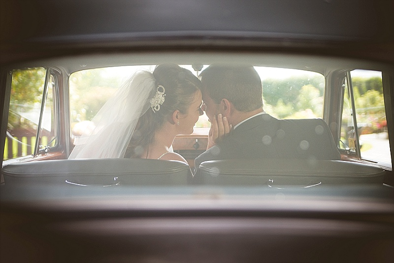 New bride and groom sitting in car looking through the window