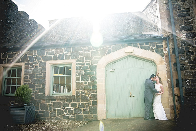 Newly married couple kiss against rustic gate with the sun in the background
