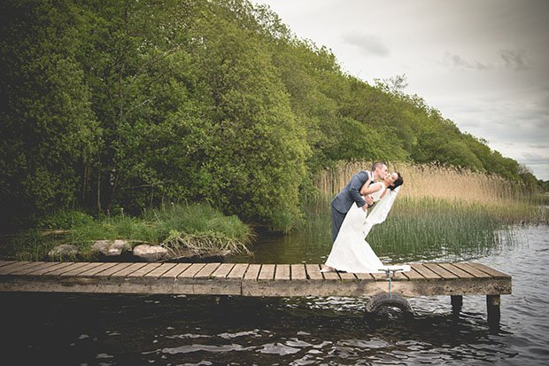 Newly married couple kiss on loughside pier