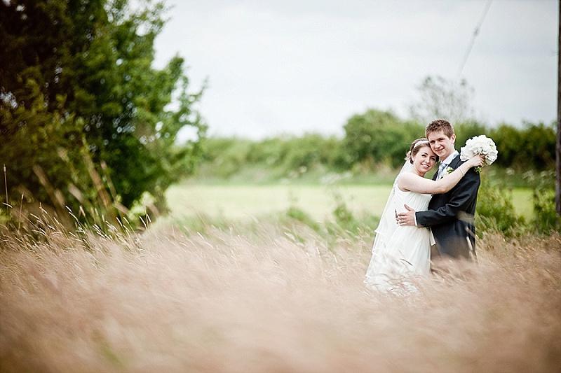 Wedding couple across long grass field