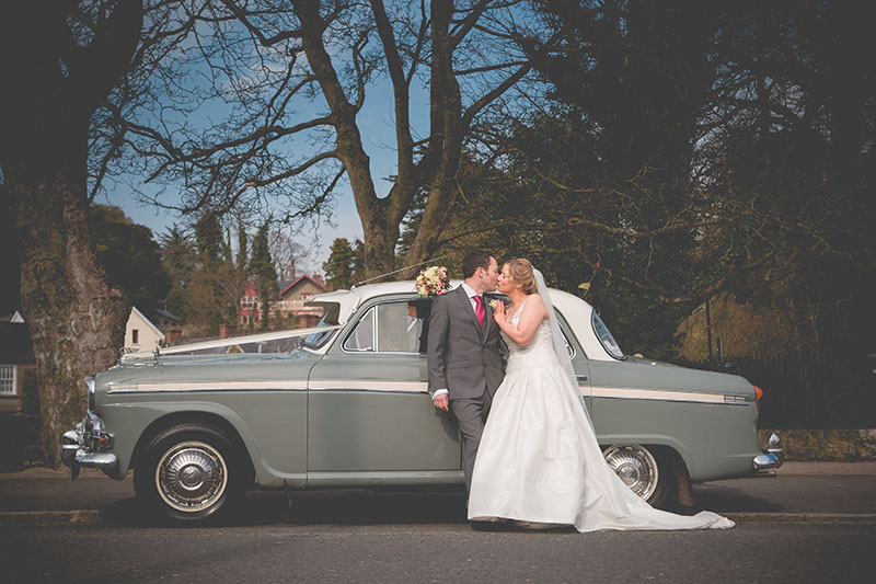 Wedding couple kiss in front of vintage 1950's wedding car