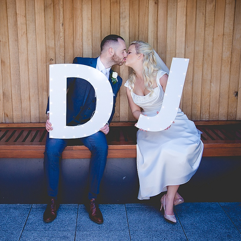 Wedding couple kiss with large oversized letters