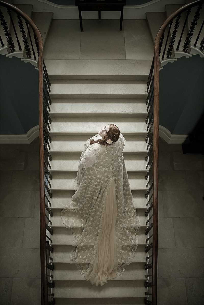 Bride stands with long dress on romantic country house stairs