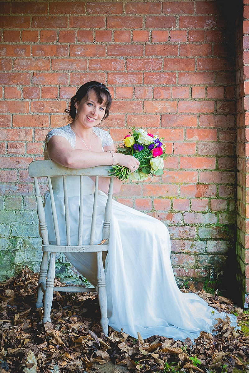 Bride with colourful flowers sits on vintage chair