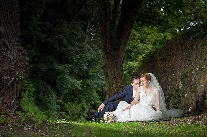 Fairytale wedding couple sit on the ground with groom kissing the bride's neck