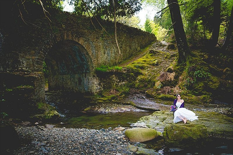 Outdoor bride sitting on rock in the middle of the river Game of Thrones