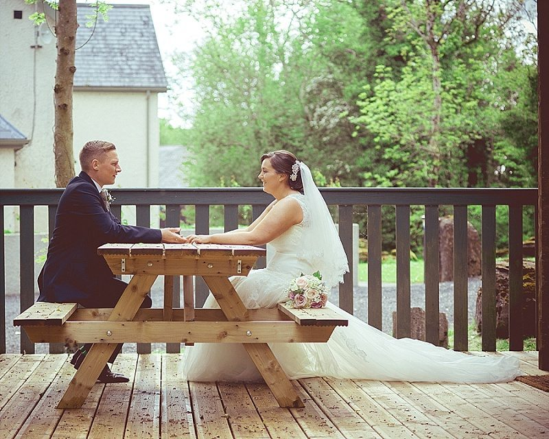 Bride and groom sit at picnic bench