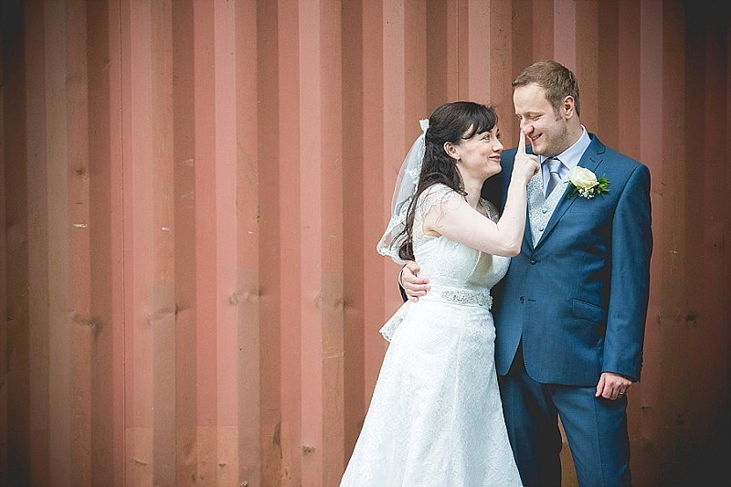 Cute bride pokes groom's nose in front of shipping container