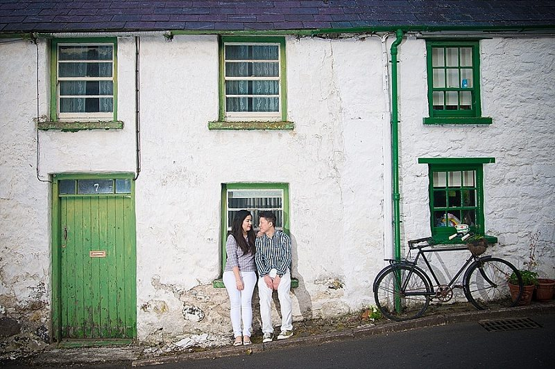Engaged couple sit on wall of rustic home with bicycle