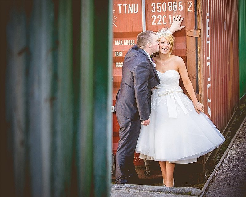 Newly married couple kiss against shipping container