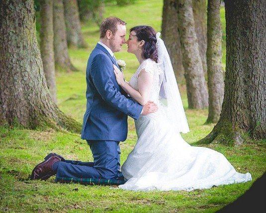 Wedding couple kneeling on ground kissing