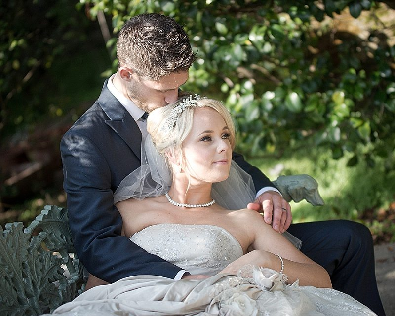 Groom Kissing top of Brides head as she rests on him