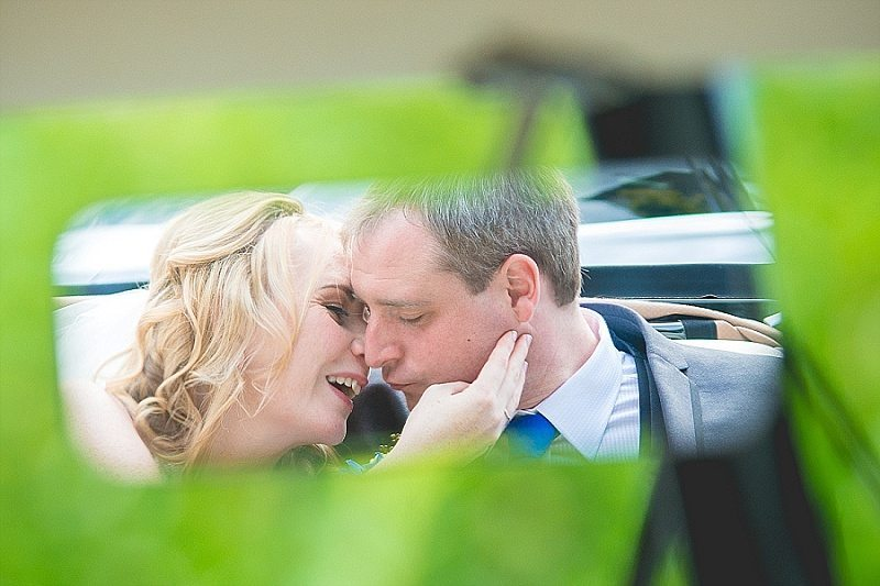 Reflection of bride and groom in Car Rear view Mirror