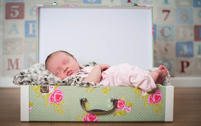 Photo of a young baby fast asleep in a suitcase bed