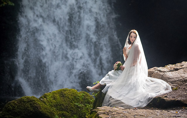 Newly married bride sits on rocks with a beautiful waterfall as a backdrop
