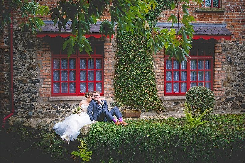 Bride and Groom sitting on Wall with at Mill