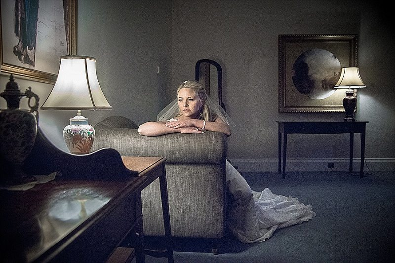 Bride sitting looking thoughtful over arm of sofa