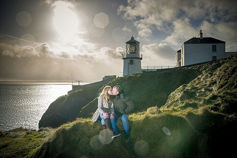 Couple kissing on grass with lighthouse