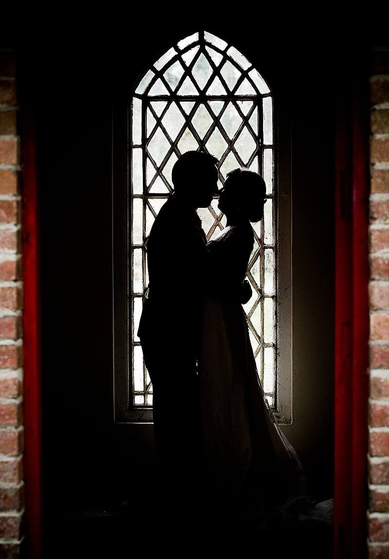 Silhouette of bride and groom nect to fill length leaded window