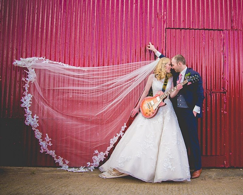 Bride and Groom standing with Guitar against red barn