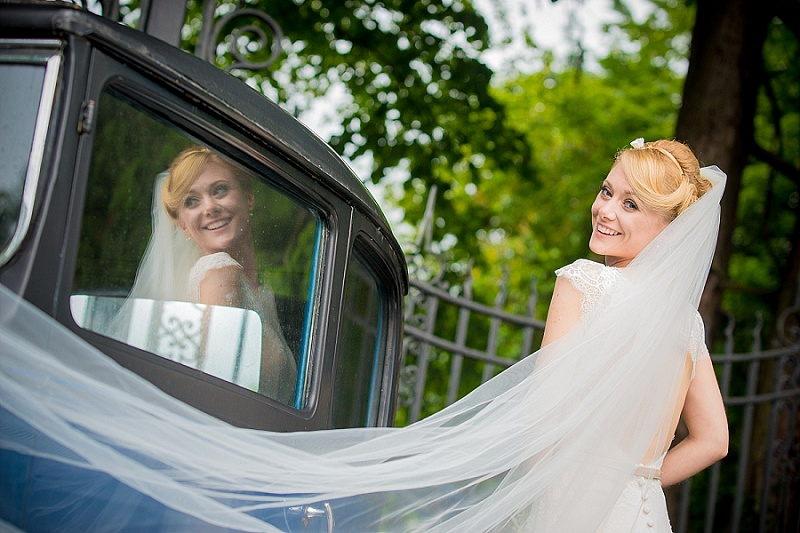 Bride with sweeping veil next to vintage car