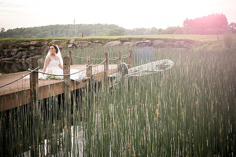Bride Sitting In Jetty surounded by Reeds