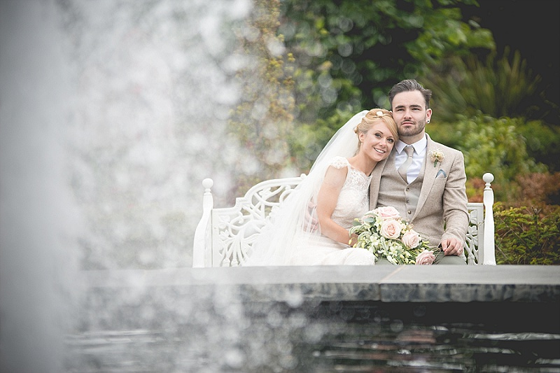 Bride and Groom sat on bench with fountain