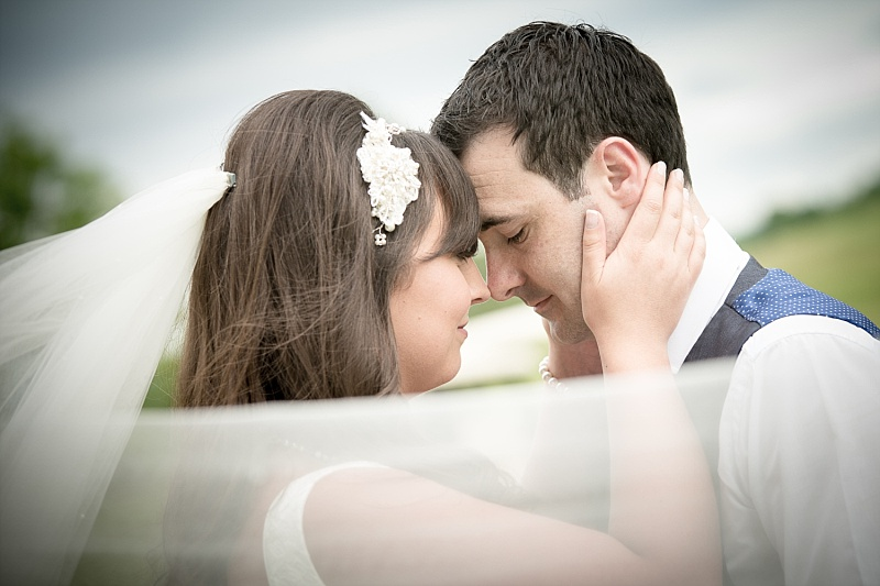 Bride and Groom heads together veil in forground